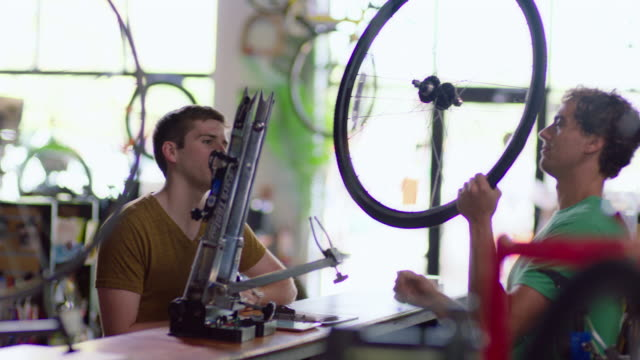 bike shop customer brings bicycle wheel for mechanic to put on truing stand and spin - calliper stock videos and b-roll footage