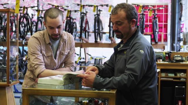 ms bike shop employee and customer browsing catalogue / portland, oregon, usa - portland oregon bike stock videos & royalty-free footage
