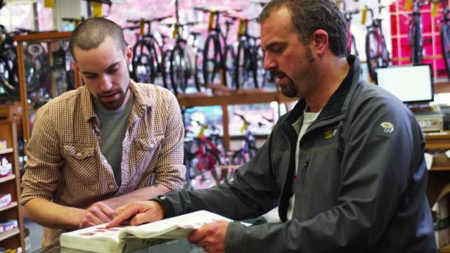 stockvideo's en b-roll-footage met ms bike shop employee and customer browsing catalogue / portland, oregon, usa - mouw