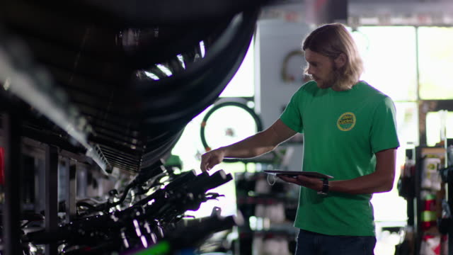 bike shop employee hangs price tags on new bicycles and manages prices on tablet computer - kleinunternehmen stock-videos und b-roll-filmmaterial