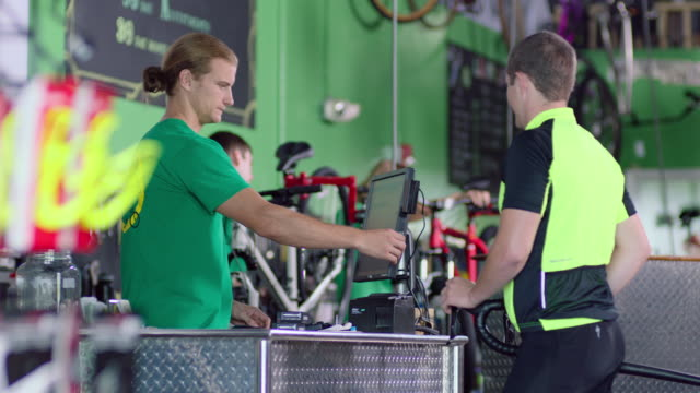 Bike shop employee swipes credit card and returns it to cyclist customer at sales counter
