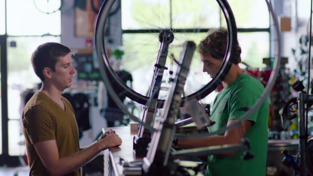 Bike shop mechanic chats with customer while bicycle wheel spins on truing stand