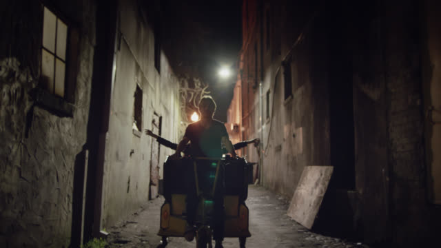 WS SLO MO. Bike taxi driver takes shortcut through city alleyway and pumps fists in air.