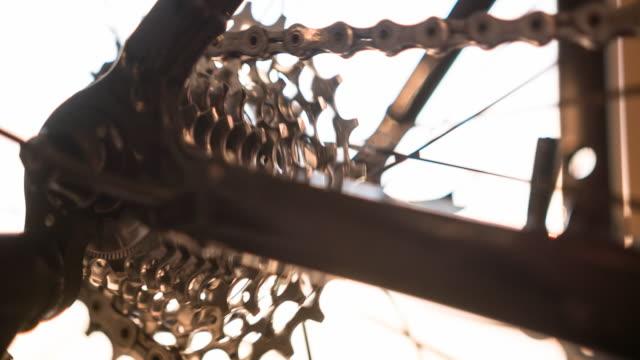 cykelhjulet, kugghjul och kedja i rörelse, upplyst av solljus - landsväg bildbanksvideor och videomaterial från bakom kulisserna