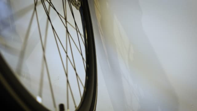 bike wheel spins in front of white wall - wheel stock videos & royalty-free footage