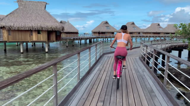 bike: woman riding bike down boardwalk on ocean by huts in bora bora, french polynesia - bora bora stock videos & royalty-free footage