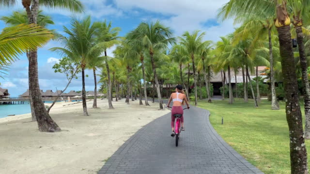 vídeos de stock, filmes e b-roll de bike: woman riding bike on path through vibrant green palm trees in bora bora, french polynesia - polinésia francesa