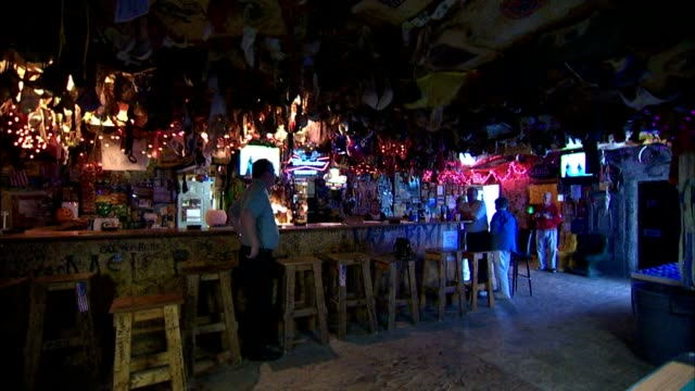 Biker amp sports bar ceiling covered with tee shirts and womens bras of all sizes hanging down Oddity wacky