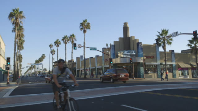 biker and cars on oceanside street, wide shot - oceanside stock videos and b-roll footage