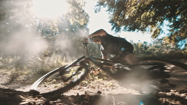 slo mo mtb biker carving through turn - andare in mountain bike video stock e b–roll