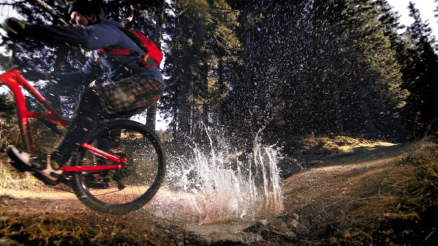 speed ramp biker causing a big splash when crossing a puddle in the forest - mud stock videos & royalty-free footage