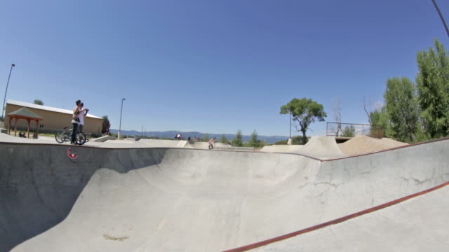 a bmx biker does a peg grind on a rail at a skate park in idaho - bmx cycling stock videos and b-roll footage