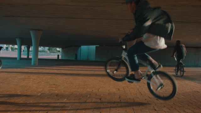 bmx biker driving around on a urban place - bmx cycling stock videos and b-roll footage