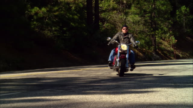 MS Biker driving motorcycle on road in Sierra National Forest / Fresno County, California, USA