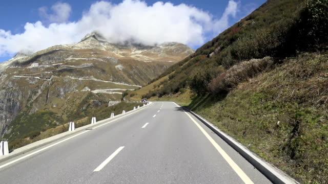 Biker driving on the Furka mountain pass road in Switzerland