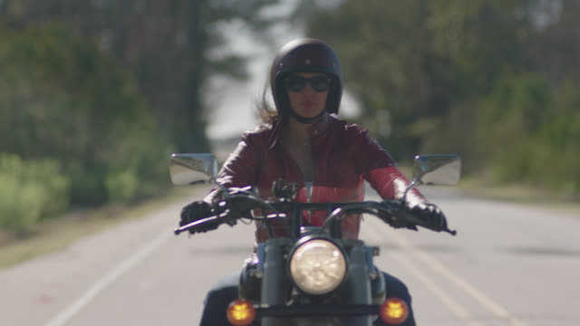 biker girl in leather jacket drives down empty road on motorcycle. - motorradfahrer stock-videos und b-roll-filmmaterial