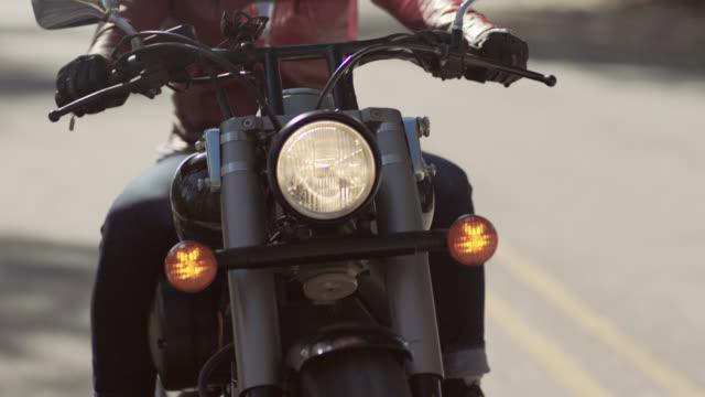 slo mo. biker girl in leather jacket drives motorcycle away from flashing police lights. - バイカー点の映像素材/bロール