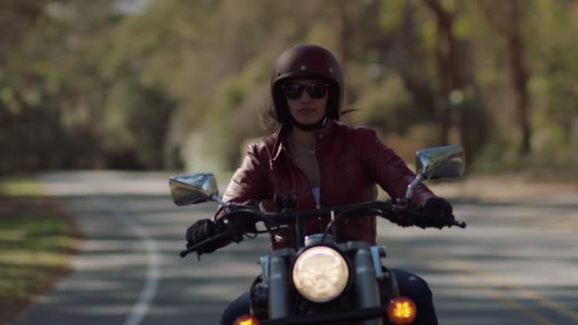 biker girl in leather jacket speeds down bumpy country road on motorcycle. - biker jacket stock videos and b-roll footage