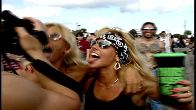 vídeos y material grabado en eventos de stock de biker girls posing for pics with tattooed man in daytona florida - sin camisa