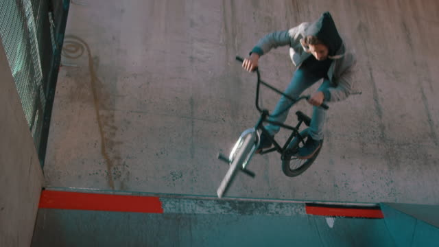 bmx biker jumping in bike park - bmx cycling stock videos and b-roll footage