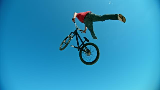 vídeos de stock, filmes e b-roll de biker velocidade rampa saltando para o ar e fazendo um truque em sua bicicleta de dj no sol - inclinação