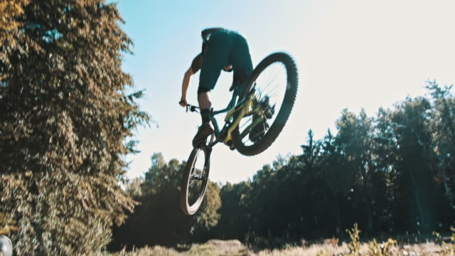 slo mo mtb biker jumping over the camera - mountain bike video stock e b–roll