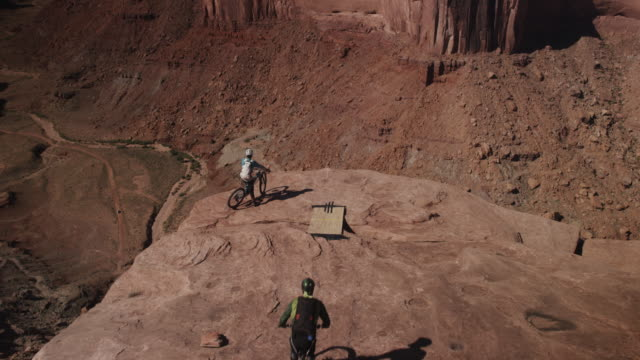 biker jumps off cliff with parachute, slow motion - moab utah stock videos and b-roll footage