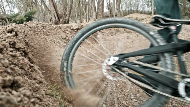 slo mo biker kicking sand on a dirt trail - mountain bike video stock e b–roll