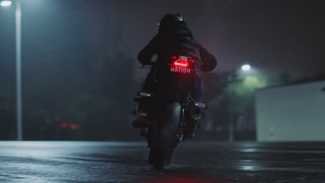 vídeos y material grabado en eventos de stock de slo mo. biker kicks up water with spinning tires as he drives past camera on rainy street at night. - luz trasera