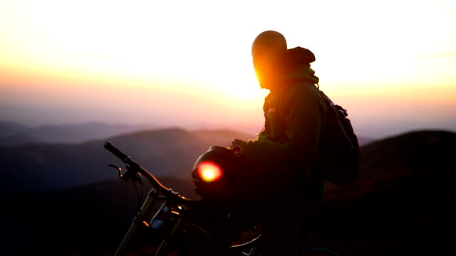 biker on top of mountain enjoys beautiful sunrise - hard hat stock videos & royalty-free footage