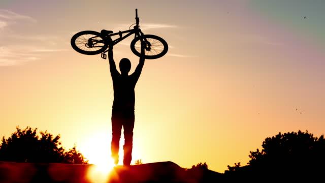 slo mo biker raising his dirt jump bike high into the air at sunset - jump shot stock videos and b-roll footage