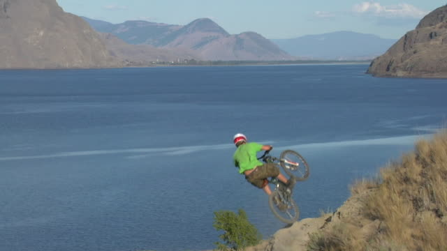 ws bmx biker riding and jumping, sea with mountains in background / california, usa - freestyle bmx stock videos and b-roll footage
