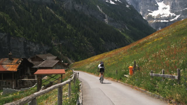 biker riding down a mountain road through the Swiss alps