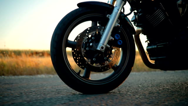 biker riding motorcycle on an empty road at sunset - wheel stock videos & royalty-free footage