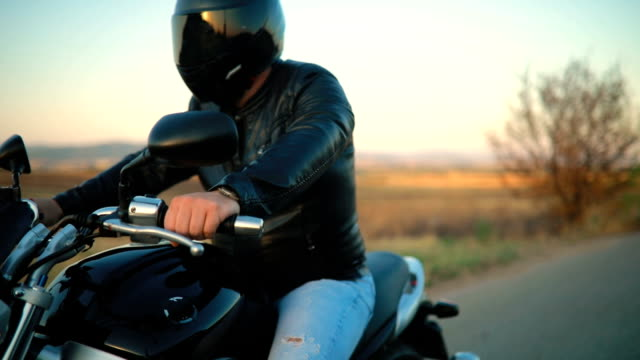 biker riding motorcycle on an empty road at sunset - crash helmet stock videos & royalty-free footage