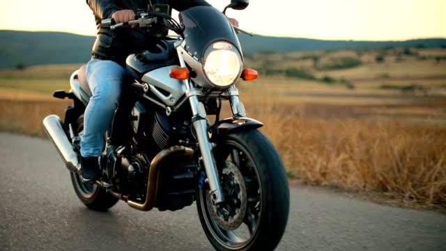 biker reiten motorrad auf einer leeren straße bei sonnenuntergang - motorradfahrer stock-videos und b-roll-filmmaterial