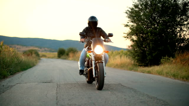 biker riding motorcycle on an empty road at sunset - motorbike stock videos & royalty-free footage