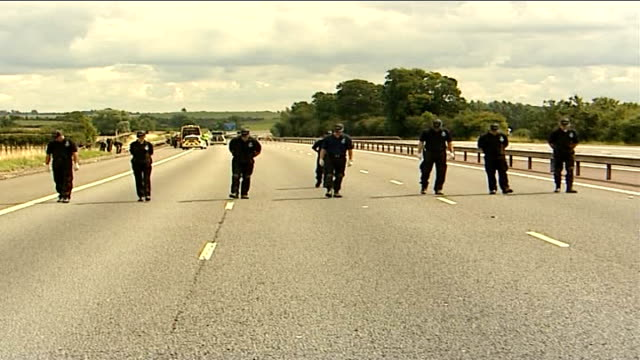 gangs may be involved in murder police officers walk in line up empty motorway looking for clues to biker shooting crane lifting dead man's... - biker gang stock videos & royalty-free footage