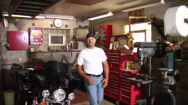 ms ts portrait biker standing next to motorcycle in garage/ man walking up to camera and folding arms/ appleton, wisconsin - goatee stock videos & royalty-free footage
