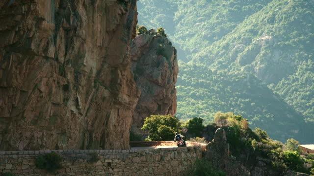 biker takes a turn on a beautiful windy mountain road, medium shot, morning - カランシェ点の映像素材/bロール