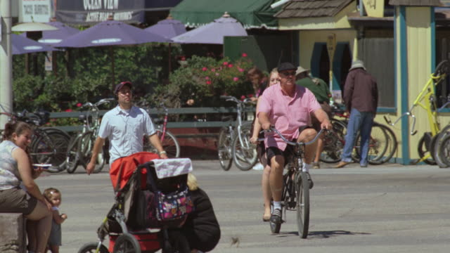 TS Bikers and pedestrians enjoying a sunny day along a paved path near storefronts / California, United States