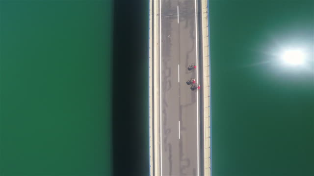 Bikers crossing a long asphalt bridge over the water