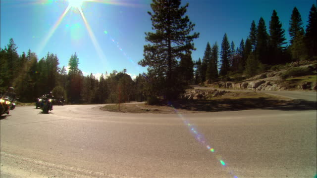 vídeos de stock e filmes b-roll de ws bikers driving motorcycles on curvy road in sierra national forest / fresno county, california, usa - capacete moto