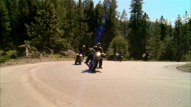 ws pan bikers driving motorcycles on curvy road in sierra national forest / fresno county, california, usa - 国有林点の映像素材/bロール