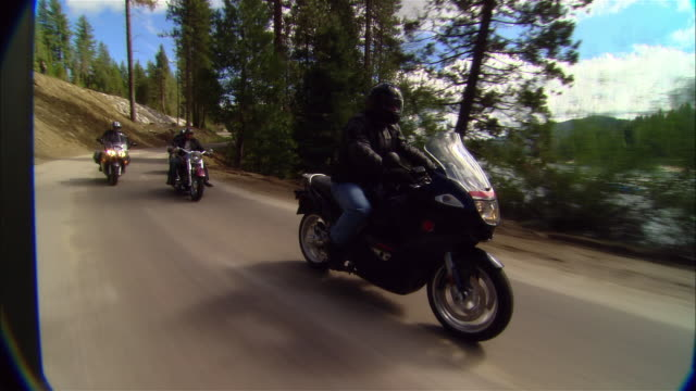 ms bikers driving motorcycles on curvy road near shaver lake in sierra national forest / fresno county, california, usa - biegung stock-videos und b-roll-filmmaterial
