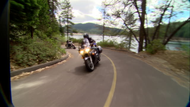 ws bikers driving motorcycles on curvy road near shaver lake in sierra national forest / fresno county, california, usa - 国有林点の映像素材/bロール