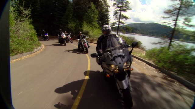 ms bikers driving motorcycles on curvy road near shaver lake in sierra national forest / fresno county, california, usa - 国有林点の映像素材/bロール