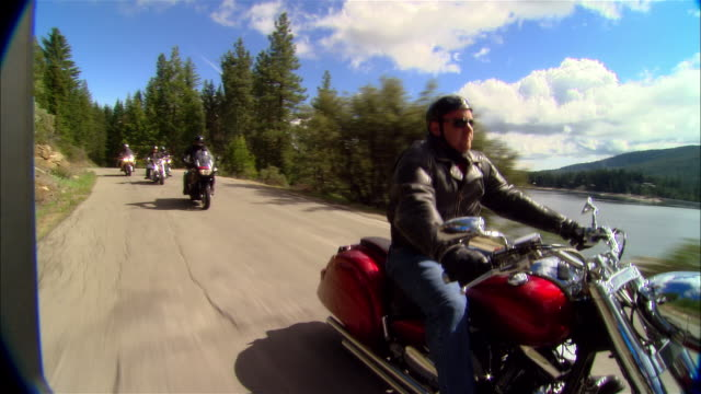 ms bikers driving motorcycles on road near shaver lake in sierra national forest / fresno county, california, usa - 国有林点の映像素材/bロール