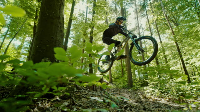 super slo mo mtb bikers jumping over a wooden ramp in a sunny forest - bicycle trail outdoor sports stock videos & royalty-free footage