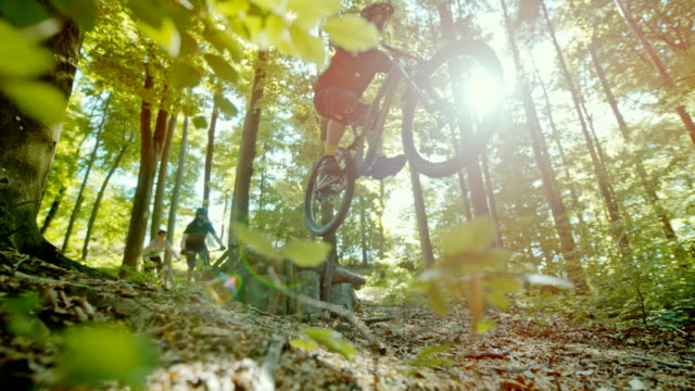 super slo mo mtb bikers jumping over a wooden ramp in a sunny forest - recreational horse riding stock videos & royalty-free footage